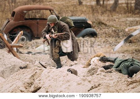 Gomel, Belarus - November 26, 2016: Re-enactor Dressed As Red Army Russian Soldier Of World War II Running On Battlefield. Celebration Of 73rd Anniversary Of Liberation Of Gomel From Nazi Invaders
