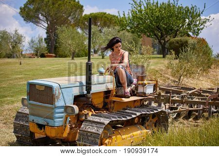 Young farmer woman on the vintage  tractor