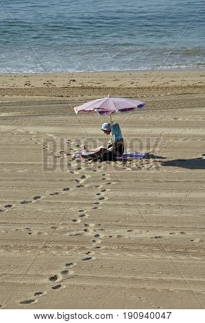 Algarve, Portugal, 24-September-2007: A middle aged woman sitting underneath a parasol on the beach in Portugal.