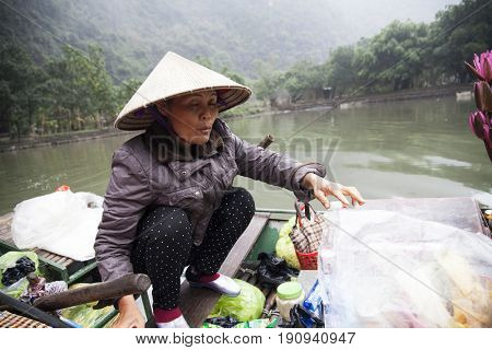 Tam Coc, Ninh Binh, Vietnam - March 16, 2017: Vendor trying to sell some fruits and drink to tourists on the river, Tam Coc, Vietnam