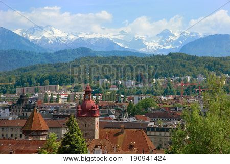 Beautiful view of Lucerne and the snowy Alps over the roofs of historical buildings (town hall tower water tower etc.)