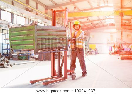 Full length of young manual worker pushing hand truck with heavy metal in industry