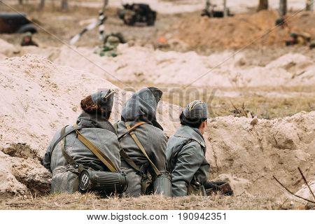Unidentified Women Re-enactors Dressed As German Wehrmacht Military Radio Operators In World War II Hidden Sitting In Trench In Autumn Battlefield During Historical Reenactment.