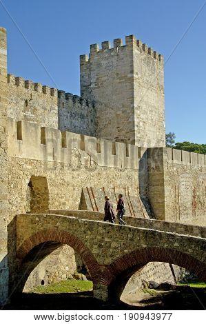 Alentejo, Portugal, 27-September-2007: Two people walking into an impressive ancient castle in Evora.