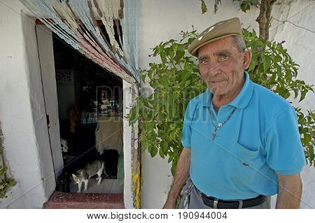Alentejo, Portugal, 25-September-2007: An old Portuguese man in a bright blue shirt standing in front of his house where two cats are lurking in the doorway in Mertola village.