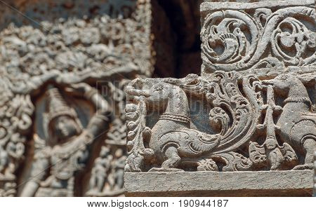 Background in Indian raditional style with reliefs and fantasy birds inside the 12th century Hoysaleshwara temple in Halebidu, Karnataka state, India