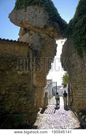 Alentejo, Portugal, 25-September-2007: A couple walking through a gate beneath a majestic clash of ancient ruins in Mertola village.