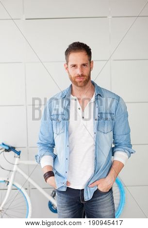 Casual guy with denim shirt and beard next to his bike looking at camera