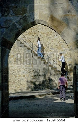 Alentejo, Portugal, 27-September-2007: Three people making their way to the top of an impressive castle in Evora.