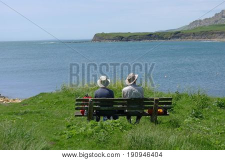 Cornwall, South England, 06-06-14: An old couple sitting on a bench and enjoying the view in Cornwall.