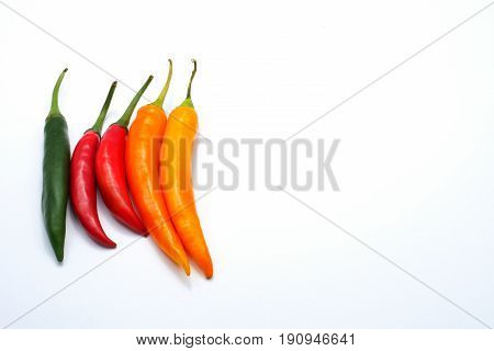 Multiple color red green yellow chilli pepper isolated on white background with copy space