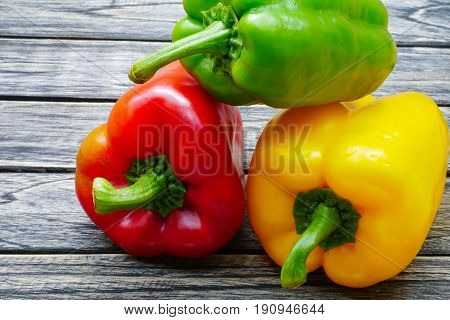 Sweet red green yellow bell pepper on wooden table background
