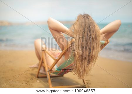 Long haired blonde girl sitting in a beach chair on vacation