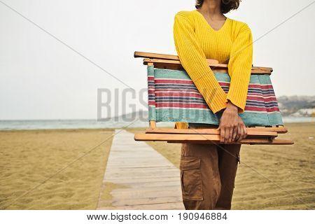 Woman carrying a beach chair