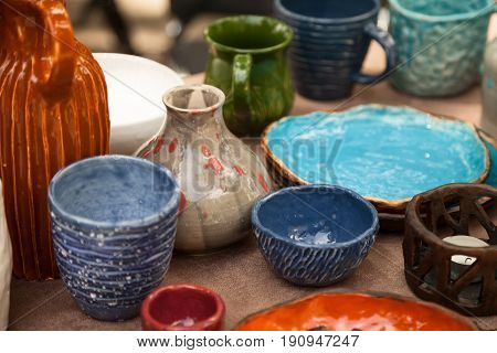 Lots of handmade tableware - ceramic cups plates at pottery shop. Colorful blue and orange clayware background