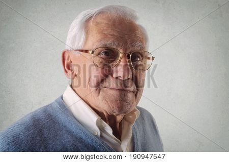 Portrait of elderly man with white shirt and light blue sweater