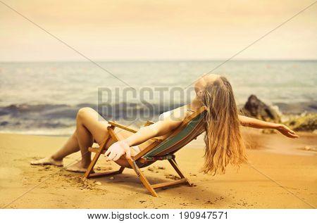 Woman with long blonde hair sitting in a beach chair