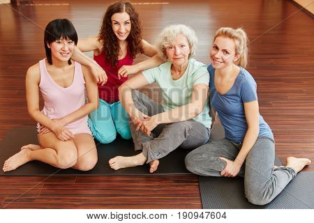 Sporty senior citizen and young women in yoga class