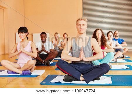 Group in yoga class meditating together at health club
