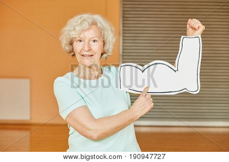 Active Senior with muscles sign at fitness studio