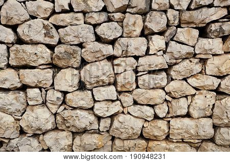 an old stone wall made of loose stone blocks - a natural rock mosaic like pattern