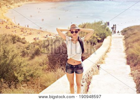 Young girl with hat and sunglasses standing on the way to the beach