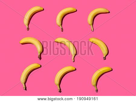 Rows of yellow ripe bananas lying on pink background.