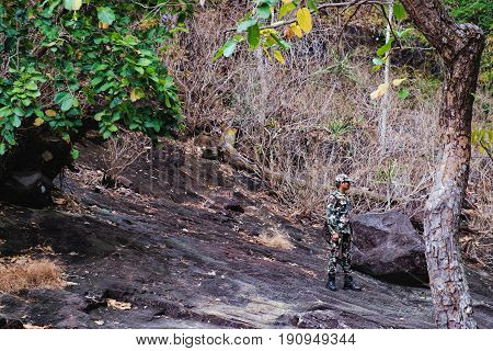 Koh Chang, Thailand - December 20, 2015: Photo of the forester in camouflage clothes standing on a stone of the Khlong Phlu waterfall Mu Koh Chang National Park, Thailand.