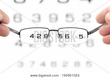 Glasses with right diopter in hands in front of an eyesight eye test chart. The glasses are in focus and the chart is out of focus.