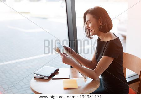 Side view of elegant adult woman sitting at table and looking through papers.