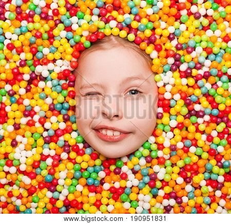 From above view of content kid winking at camera while lying in candies.