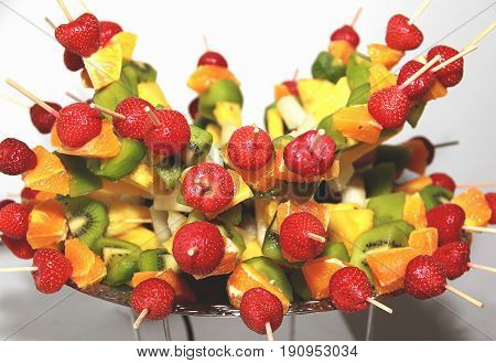 Festive food. Canape with  fresh fruits. (strawberry, pineapple, kiwi, orange)