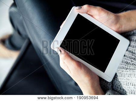 A girl holding a tablet in hands, reader with a nice manicure. Leather trousers, ugg boots. Fashion, style, learning, modern, recreation a