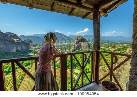 Woman tourist looking panorama from famous Monastery of Holy Trinity in Meteora, Peloponnese, Thessaly, Greece. Tourism and travel in European scenic destinations. Agia Triada is Unesco Heritage Site.