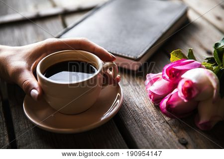 Female hand with a cup of coffee, book and flowers on wooden background. Flowers, break, work a