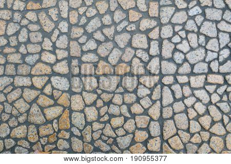 Road with cobblestone pavement with gray and brown pattern old stone texture. Can be use as background.
