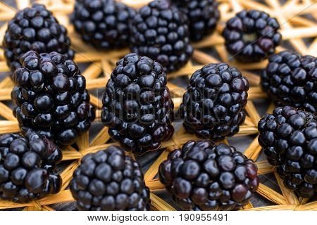 Ripe and fresh blackberries on a background of a straw mat.