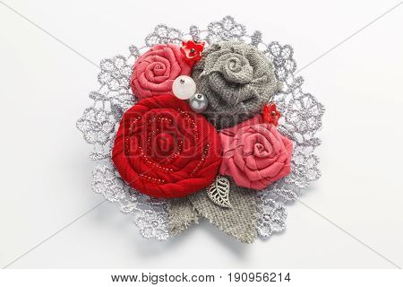 Stylish handmade brooch consisting of red flowers from fabric on a white background