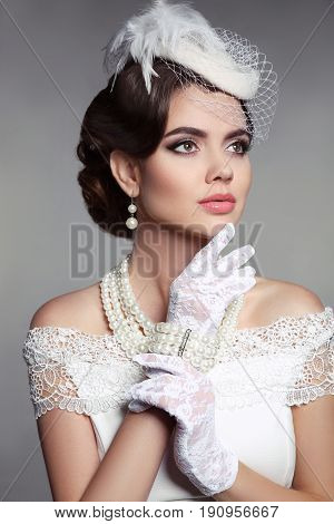 Fashion Retro elegant woman portrait. Wedding photo of beautiful brunette female in white hat, vintage gloves and pearls jewelry accessories over grey studio background.