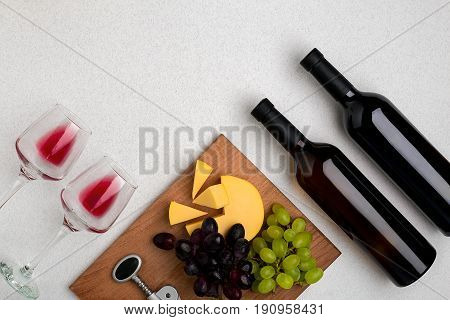 Two glasses of red wine, cheese and grapes. Two bottles of wine and a corkscrew. Top view with copy space