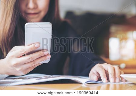 A beautiful Asian woman holding and using smart phone while reading magazines on wooden table in the bistro cafe