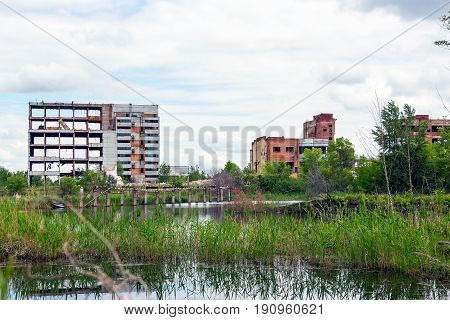 The abandoned building is located among the trees. There is a pond in front of the building. This is a former factory or office