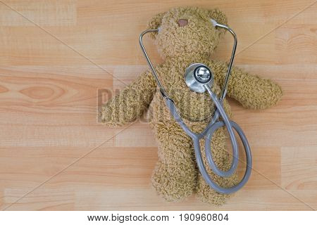 Teddy bear on wooden floor with stethoscope, acoustic medical device with earpieces in ears