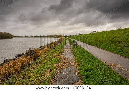 Dark clouds above a dike next to a path