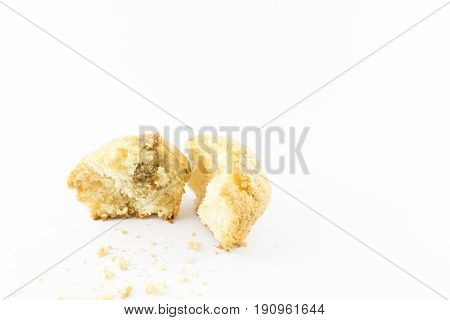 Muffin cut in half with scattered crumbs. White background.