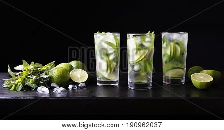 Three glasses of cocktail mojito lemonade on the bar. Refreshing Party cocktail. Lime, ice and mint on the table. Black background.