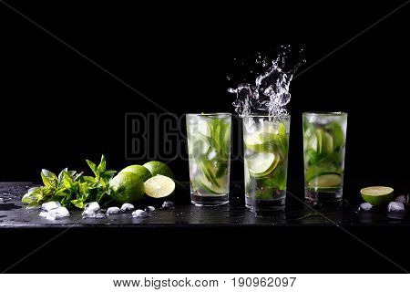 Mojito summer party refreshing tropical cocktail non alcohol drink in highball glass with splash soda water, lime juice, mint leaves, sugar, ice and rum. Dark black background with copy space text