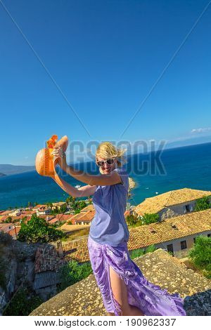 Happy tourist vacation woman with sun hat freedom at overlook of Agios Ioannis Monastery inside Koroni Castle, Peloponnese, Greece.Happiness summer holiday lifestyle concept.Europe travel destination