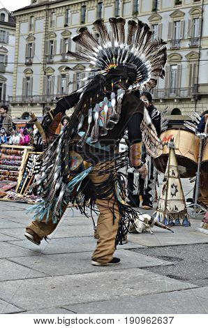 Turin, Italy - April 27, 2013: Red indian in traditional costume dancing in the center of Turin, Italy. Street performance of a group of Native Americans with sounds and traditional dancing.