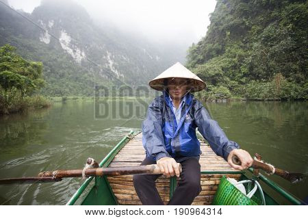 Tam Coc, Ninh Binh, Vietnam - March 1, 2017: Unidentified rower guides in a boat trip visiting rice fields and limestone mountains along the Ngo Dong river at Tam Coc, Ninh Binh, Vietnam